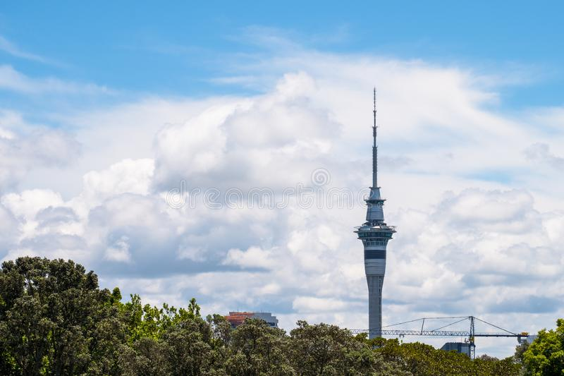2017, DEC 4 - Auckland, New Zealand - Skytower over the green trees with clouds and blue sky. I. 2017, DEC 4 - Auckland, New Zealand - Skytower over the green stock images