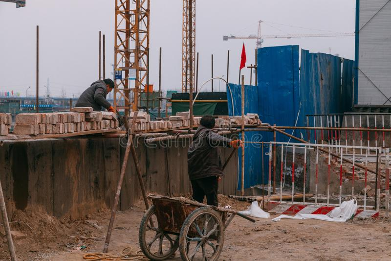 18 Dec,2014 Beijing. Two men on a construction site in City with cranes and workers stock photos