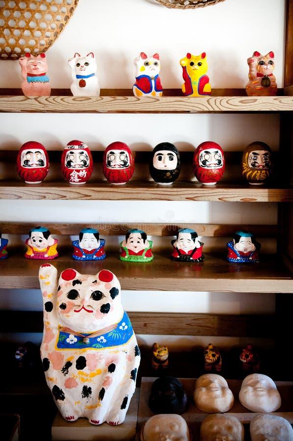 Daruma and Maneki Neko Dolls in Souvenir shop, Narita, Japan. DEC 12, 2012 Chiba, JAPAN - Vintage Japanese style souvenir, Paper mache Daruma and Maneki Neko royalty free stock image