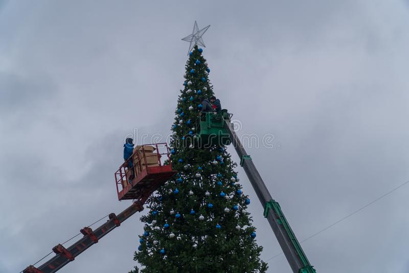 15 2017 Dec Rosja Miasto Domodedovo ashkhabad główny plaza Pracownicy wieszają świąteczne piłki na wielcy miastowi boże narodzeni zdjęcia royalty free