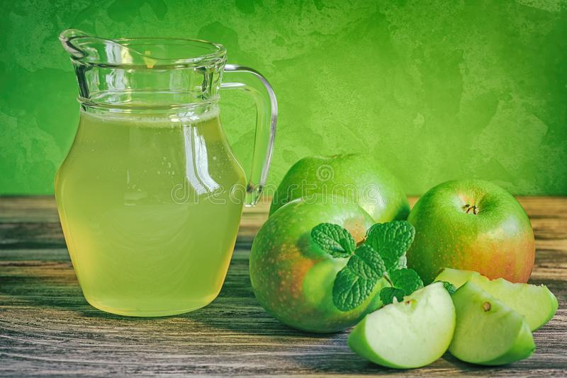 A decanter of apple juice with green apples on a wooden table, close-up royalty free stock image