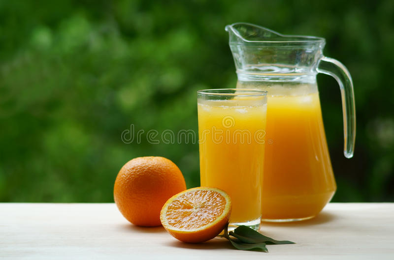 A decanter and a glass of orange juice with ice stock image