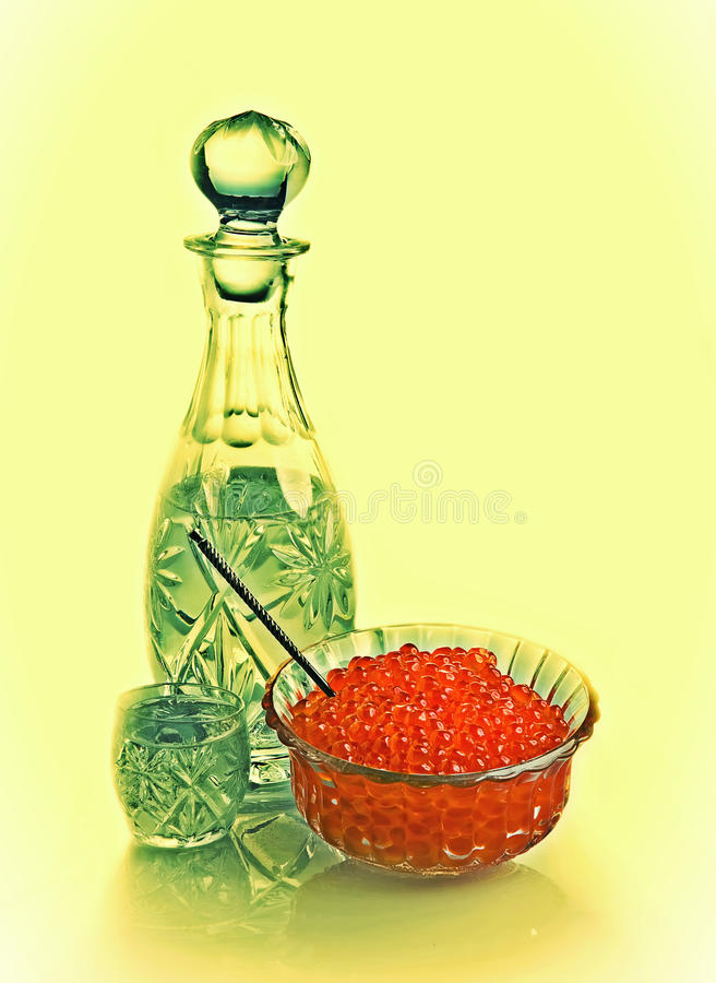 Decanter and shot glass of vodka and vase with red caviar, a vintage stock photography