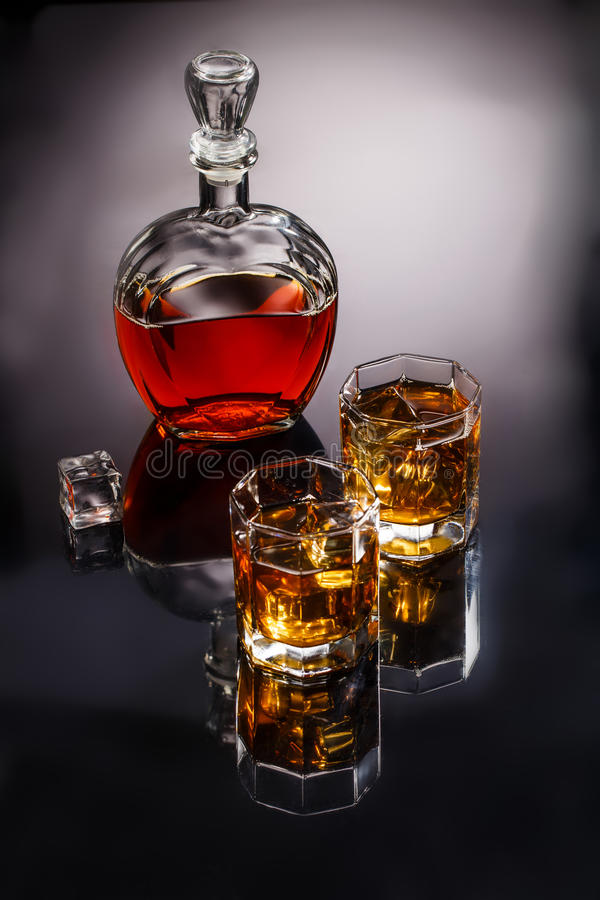 Decanter and two glasses with whisky and ice. On gray background, photo in studio stock images
