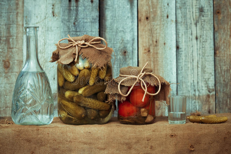 Decanter with vodka, pickles, marinated tomatoes and a shot glass in rural style, image in the soft blue toning stock images