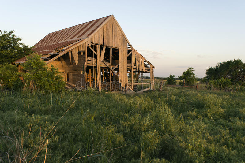 Decaying barn in a field at sunset stock photography