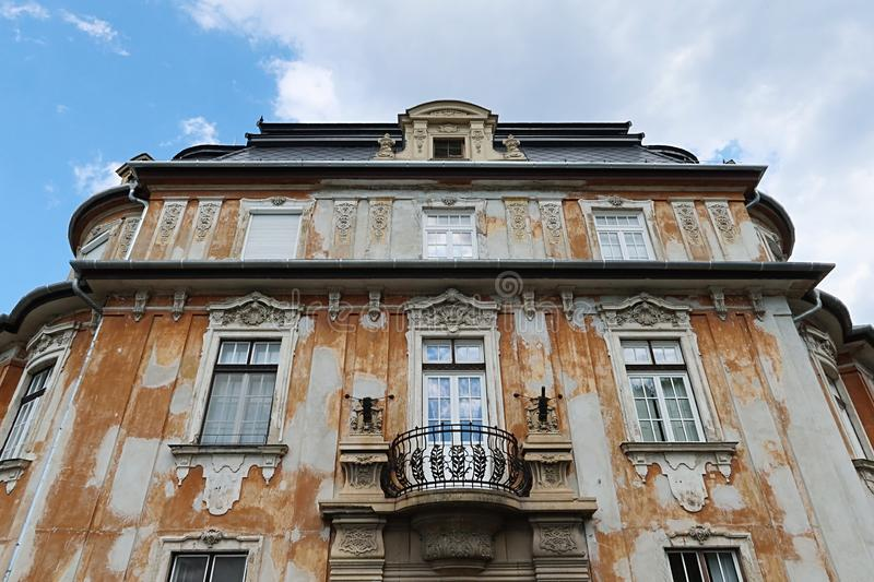 Decaying classicistic town house with typical balcony and windows, located in Esztergom, Hungary. Summer cloudy skies royalty free stock images