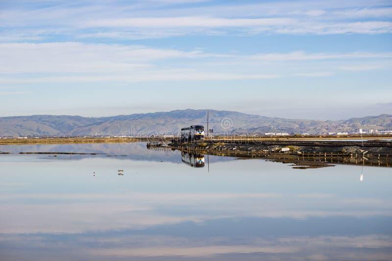 6 december, 2016, Alviso, San Jose, Californië, de V.S. - Amtrak-de trein gaat door Alviso-moeras op een zonnige dag over royalty-vrije stock afbeeldingen