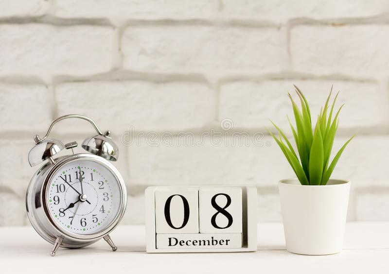 December 8,the day of the month.Calendar and alarm clock on light background, winter month, one day of the year concept royalty free stock image