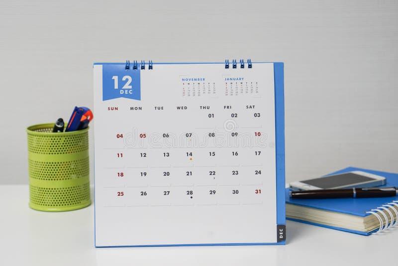 December kalender med den stationära asken och anteckningsboken på affärskvinnaskrivbordet arkivfoto