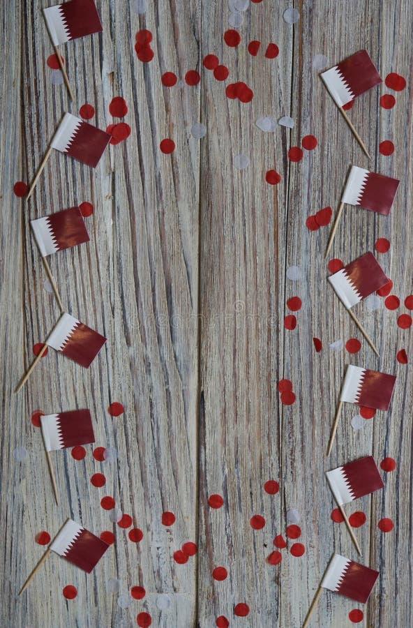 18 december onafhankelijkheidsdag van Qatar minivlaggen op houten achtergrond met papieren confetti vrolijke dag van het patriott stock foto's