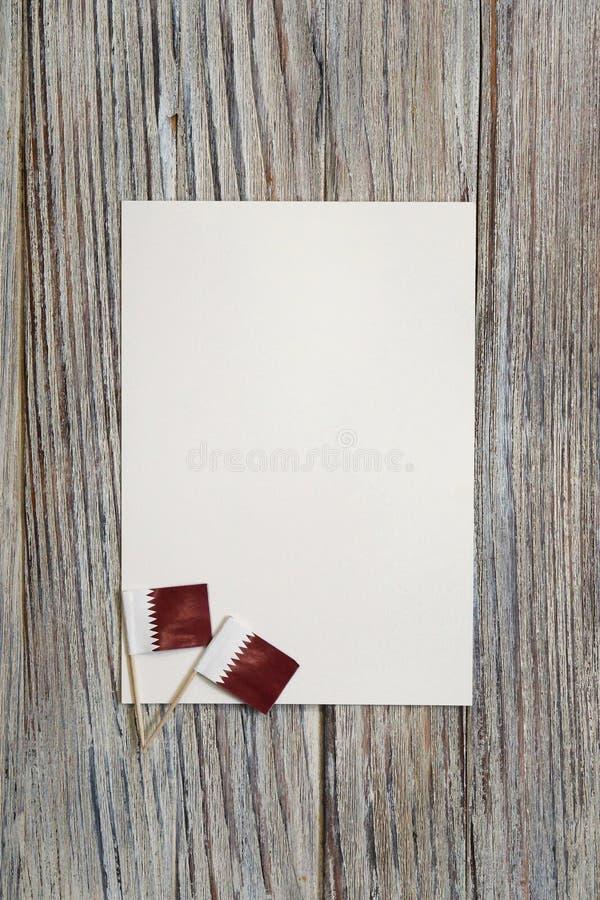 18 december onafhankelijkheidsdag van Qatar minivlaggen op houten achtergrond met wit papier stock fotografie