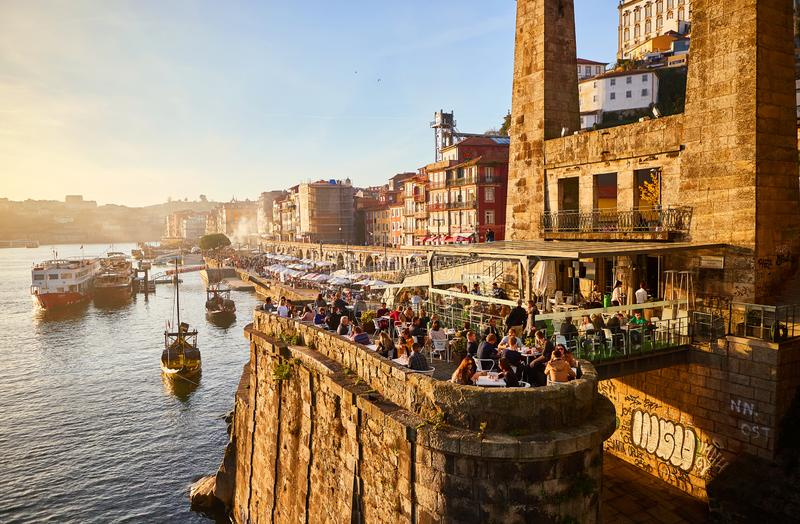 09 of December, 2018 - Porto, Portugal: Old town ribeira aerial promenade view with colorful houses, Douro river and boats. Concept of world travel stock photo