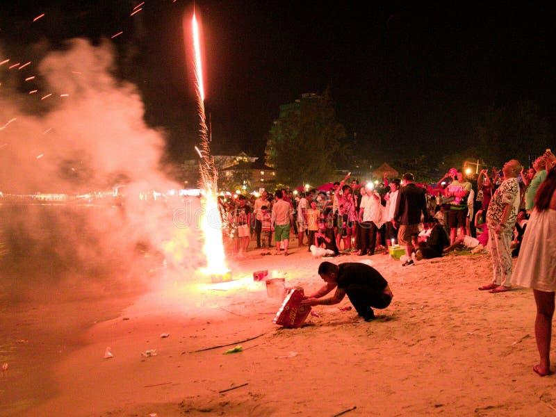31 december 2016 sihanoukville strand Kambodja, vuxen asiatisk man som knäfaller på stranden under fyrverkeriexplosion royaltyfri foto