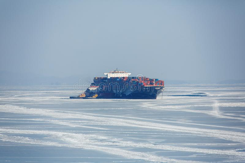 A large container ship is on the roadstead in a frozen bay near the village of Slavyanka in the Primorsky Krai. stock photography