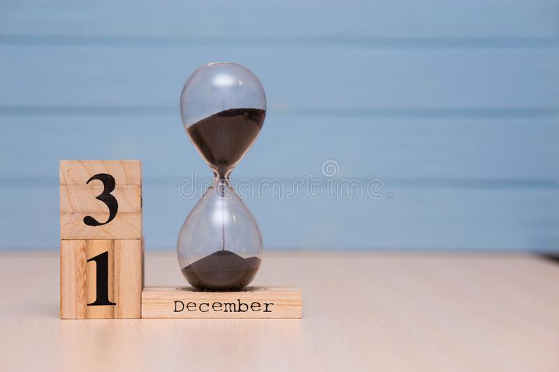 December 31st set on wooden calendar and hourglass with blue background. Calendar date stock photography