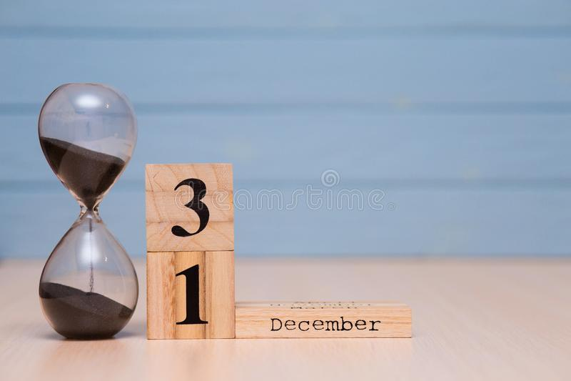 December 31st set on wooden calendar and hourglass with blue background. Calendar date stock photos