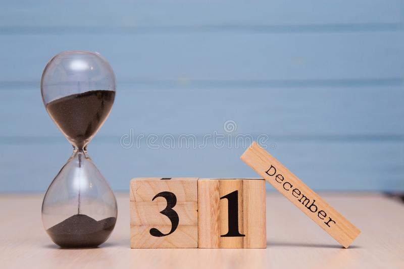 December 31st set on wooden calendar and hourglass with blue background. Calendar date stock images