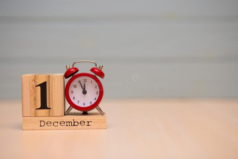 December 1st set on wooden calendar and red alarm clock with blue background. Clock face showing five minutes to midnight stock images