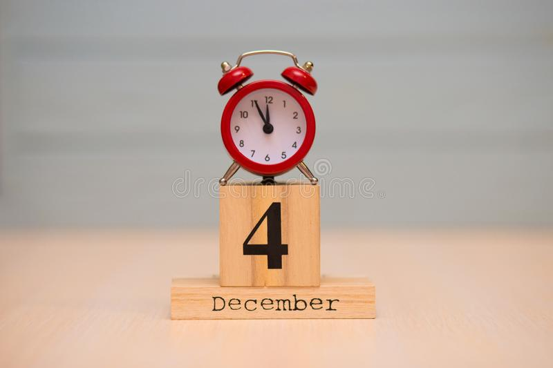 December 4th set on wooden calendar and red alarm clock with blue background. Clock face showing five minutes to midnight royalty free stock images