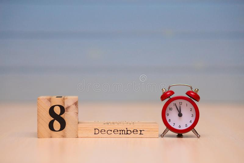 December 8th set on wooden calendar and red alarm clock with blue background. Clock face showing five minutes to midnight stock photos