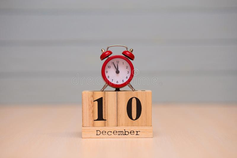 December 10th set on wooden calendar and red alarm clock with blue background royalty free stock images