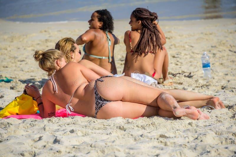 6 December 2016. Two sitting sunburnt brazilian women and two lying foreign white women in bikini at the coast of Copacabana beach royalty free stock image
