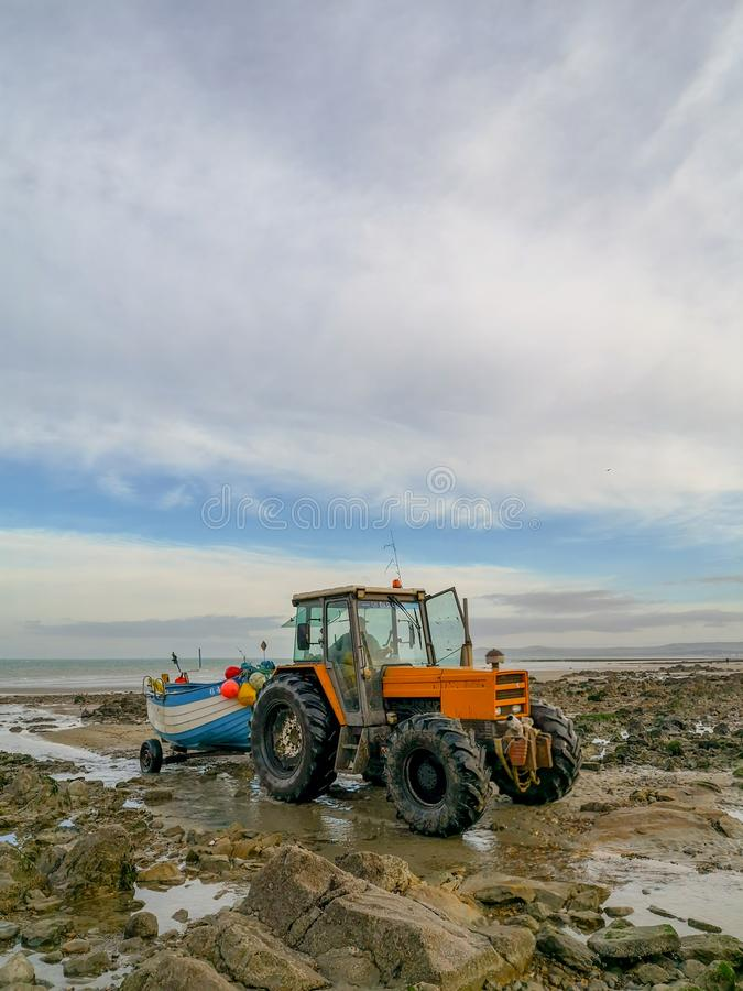 December 2018 - Wissant, France: Orange tractor towing a wooden white and blue fishing boat on a rocky beach during low tide stock photography