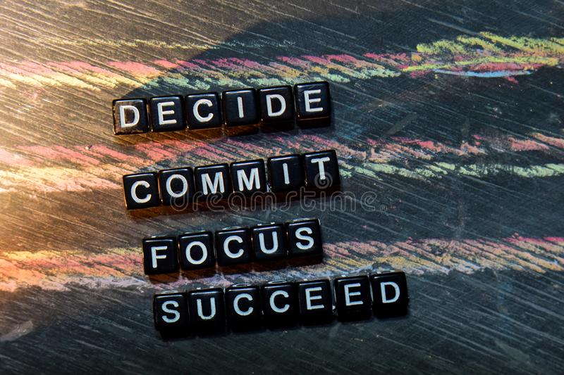 Decide Commmit Focus Succeed on wooden blocks. Cross processed image with blackboard background. Inspiration, education and motivation concepts stock image