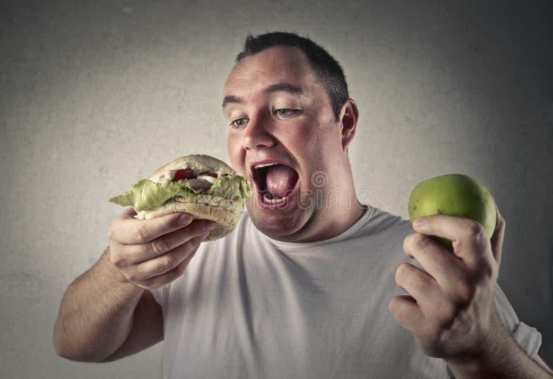 Decidendo se mangiare sano oppure no fotografia stock