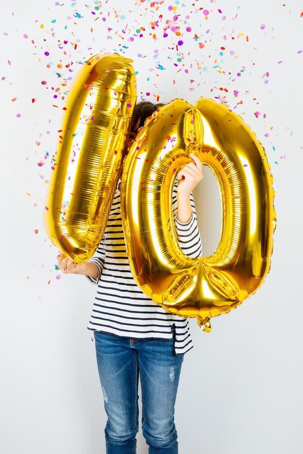 decima ragazza facile di celebrazione di anniversario con i palloni dorati immagine stock