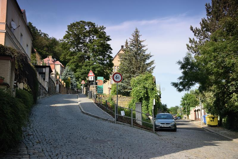Decin, Czech republic - June 14, 2019: path, car, traffic sign, houses and trees at summer sunset royalty free stock photos