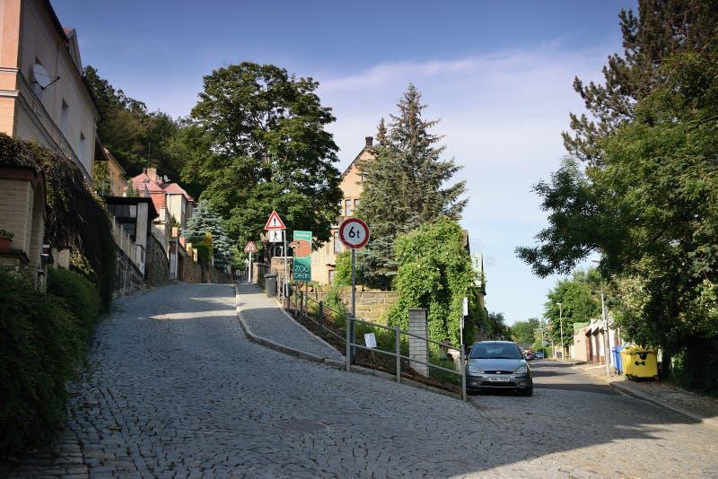 Decin, República Checa - 14 de junio de 2019: trayectoria, coche, señal de tráfico, casas y árboles en la puesta del sol del vera fotos de archivo libres de regalías