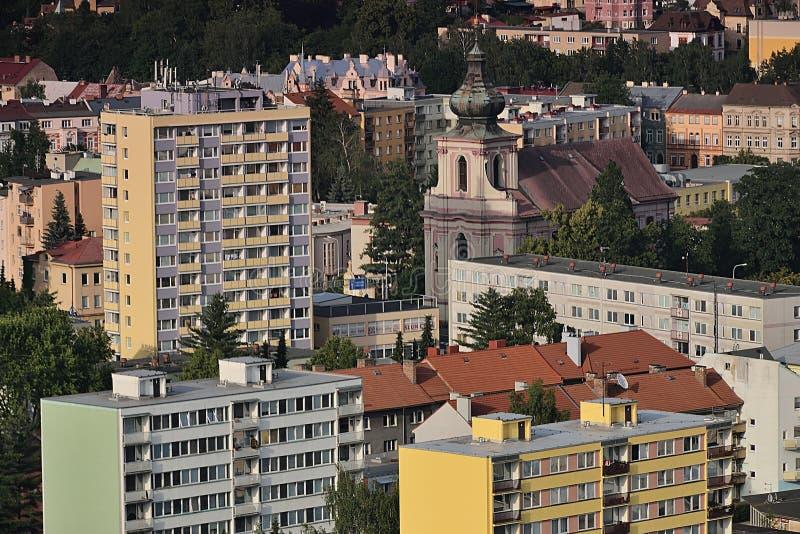 Decin, repubblica Ceca - 14 giugno 2019: chiesa fra le case di pannello osservate dalla vista di stena di Pastyrska al tramonto d immagine stock libera da diritti