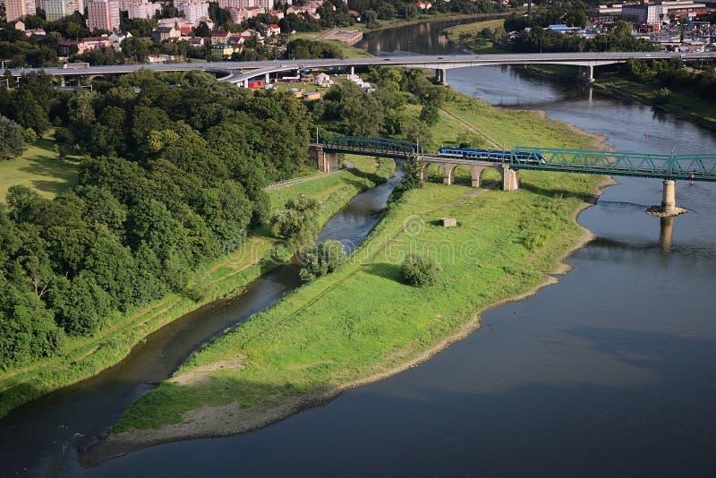 Decin, repubblica Ceca - 14 giugno 2019: treno sul ponte sopra confluenza dei fiumi Labe e Ploucnice al tramonto di estate immagine stock