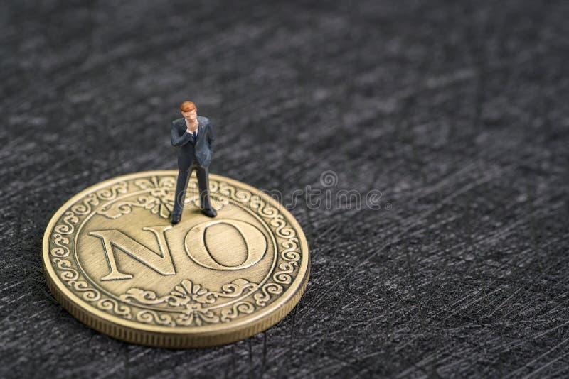 Decisión económico, riesgo de inversión, la disminución o no dice ningún concepto, hombre de negocios miniatura que piensa y que  foto de archivo libre de regalías