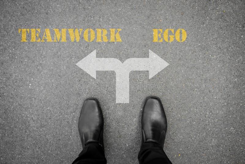 Decisión a hacer - trabajo en equipo o ego fotografía de archivo