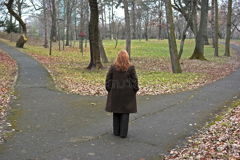 Decision. Woman approaching a crossroad (fork) in a forest, concept of decision process