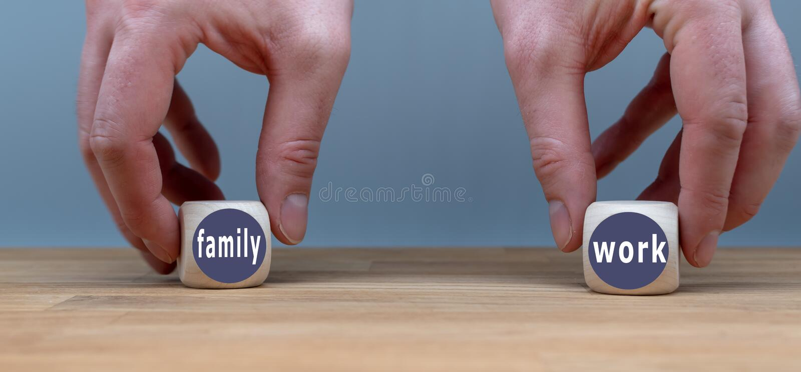 Decision between family and work. Hands hold two cubes with the words `family` and `work stock image