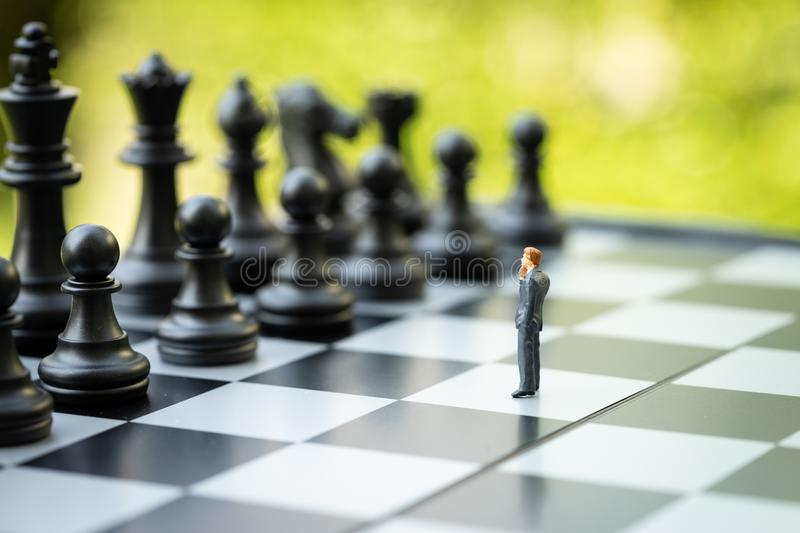 Decision making or leadership in business strategy concept, brave miniature figure businessman thinking and standing on stock photography