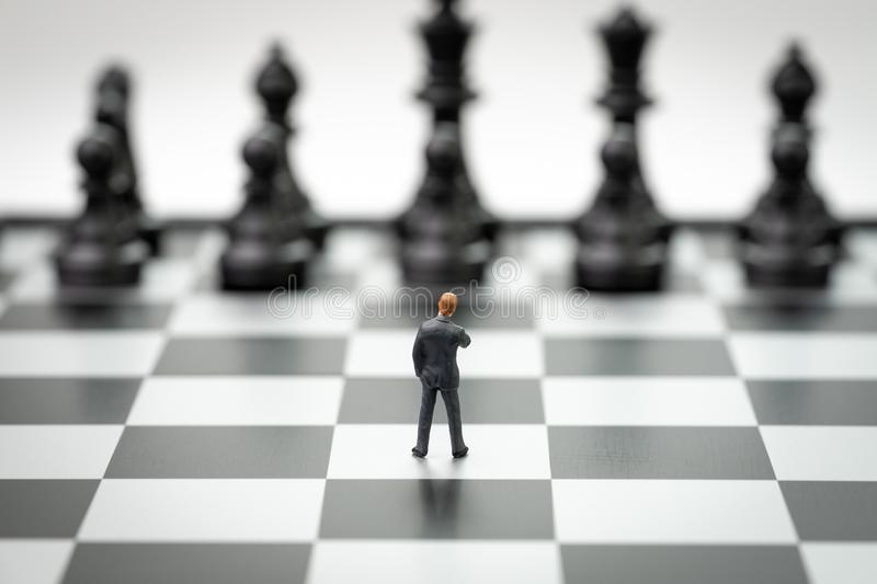 Decision making or leadership in business strategy concept, brave miniature figure businessman thinking and standing on royalty free stock photography