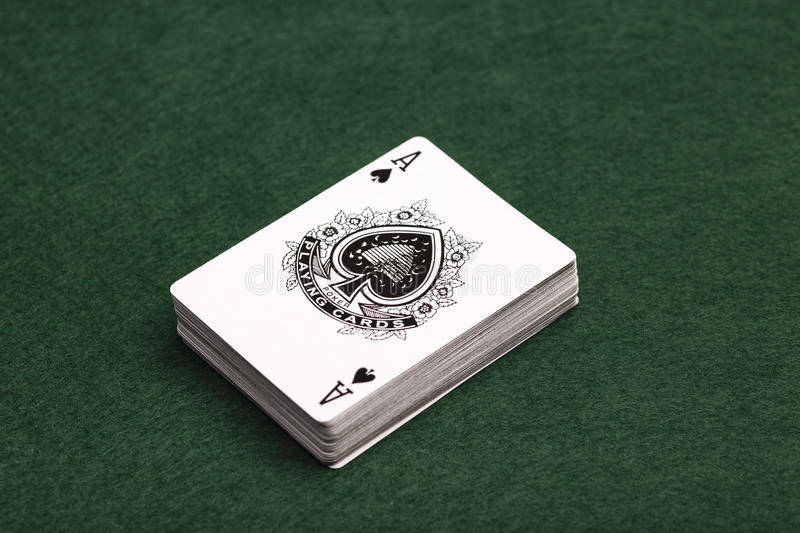 Deck Of Cards. A deck of playing-cards face up on a green baize background with the ace of spades uppermost stock photos