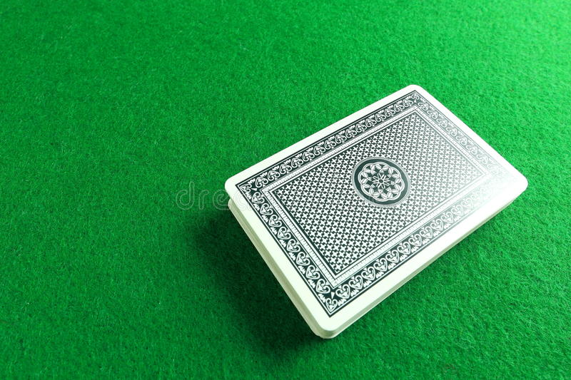 A Deck Of Cards. A deck of poker cards against green felt backdrop stock photo
