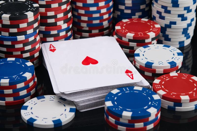 A deck of cards, surrounded by many stacks of chips to participate in gambling royalty free stock images
