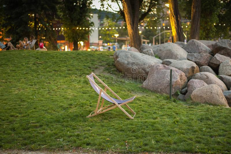 Deck chair standing on green grass at sunset in Garnizon with rocks, trees and blurred people in the background stock image
