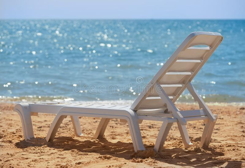 Deck chair stands on the beach, the shore of the Sea of Azov. Storm on the sea, the shore of the Sea of Azov royalty free stock image