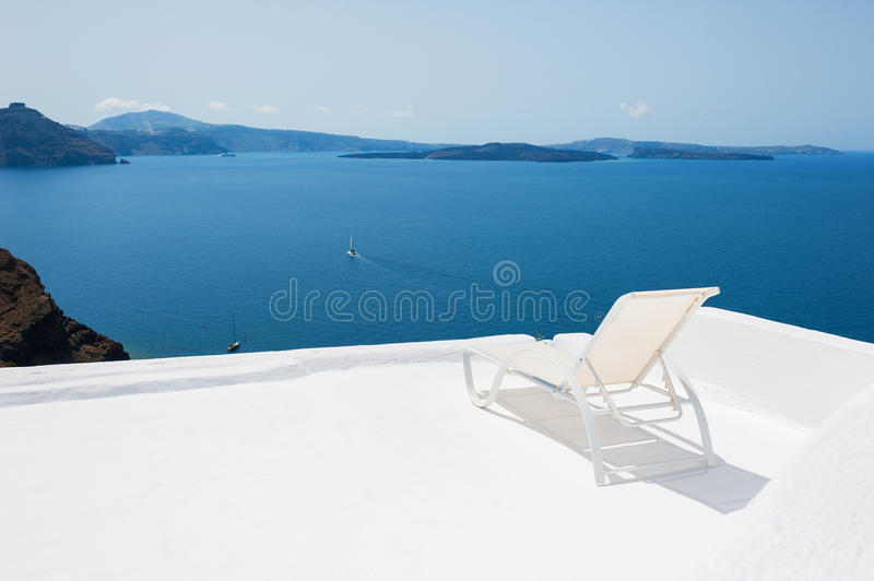 Deck chair on the terrace with sea view. White architecture on Santorini island, Greece stock photo