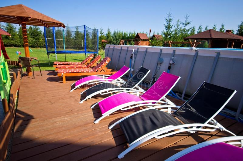 Deck chairs ar backyard swimming pool royalty free stock photography