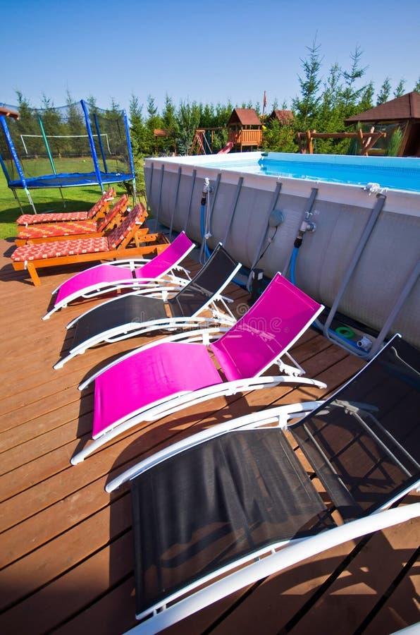 Deck chairs at backyard swimming pool stock photos