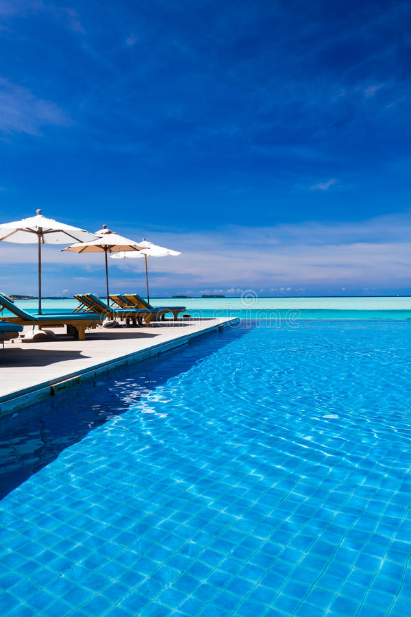 Deck Chairs And Infinity Pool Over Amazing Lagoon Royalty Free Stock Photos